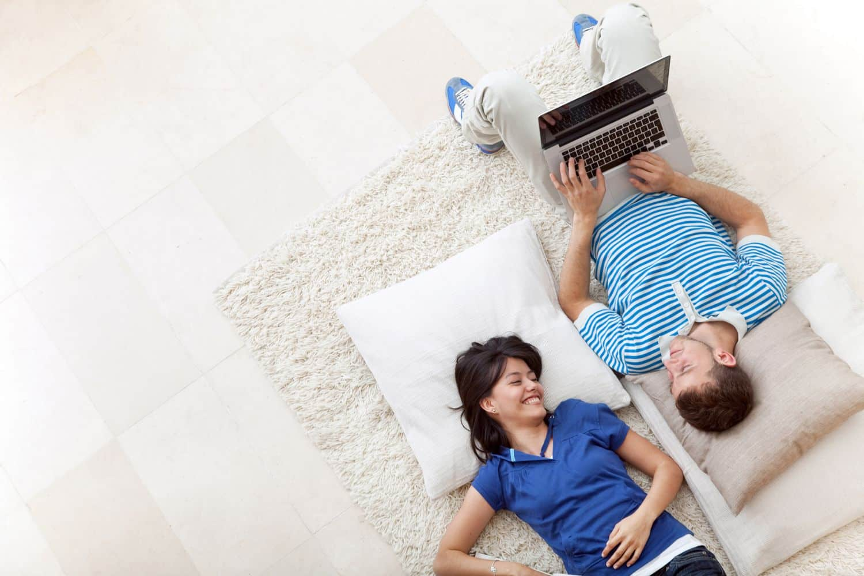 couple on floor using computer