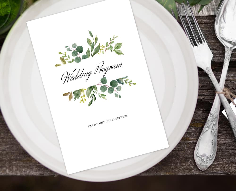 Top view of white plate with fern and silver spoon and fork with blank label on wooden table